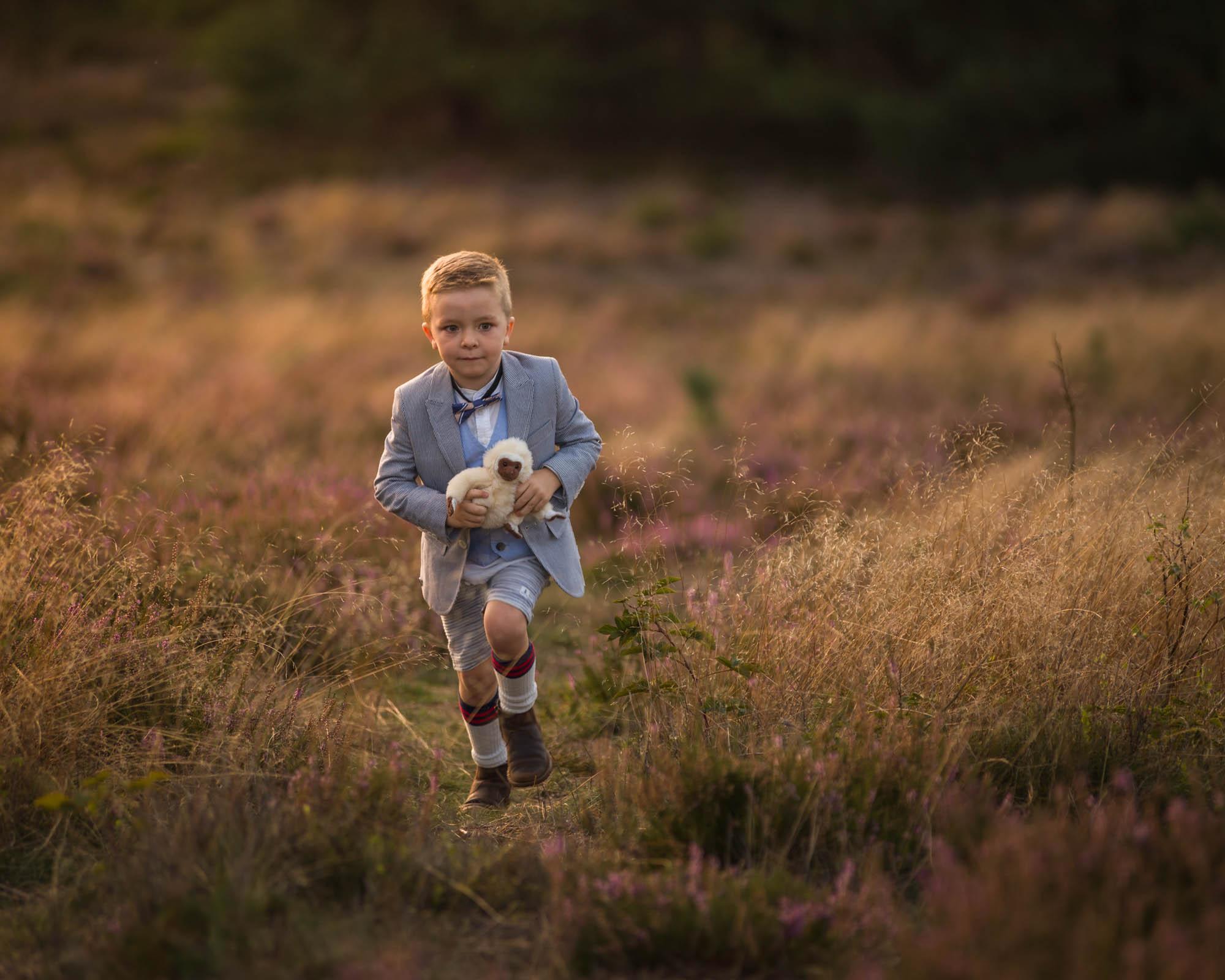 kind portret van met knuffel rennende jongen op de heide door mayrafotografie