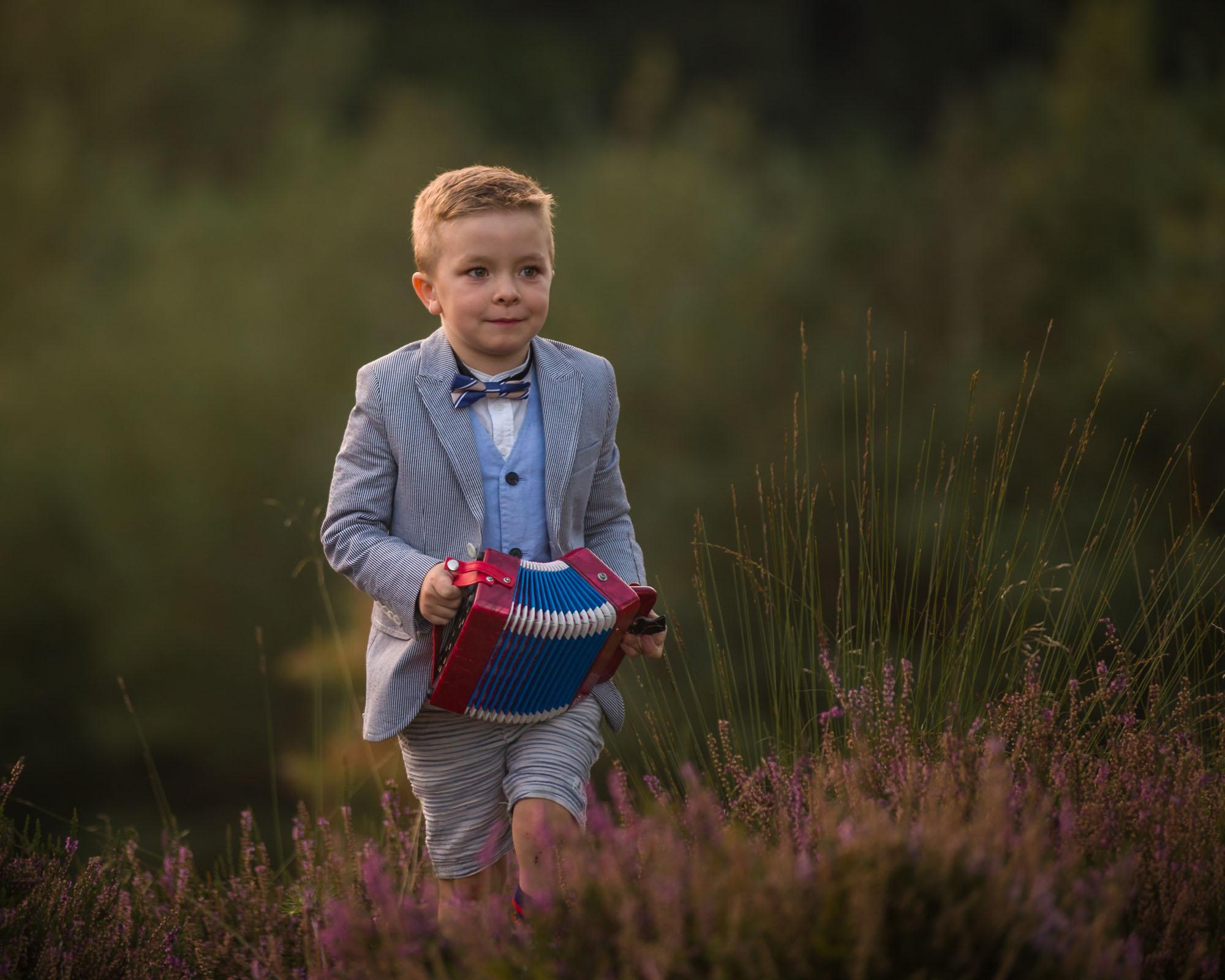 kind portret van harmonica spelende jongen op de heide door mayrafotografie