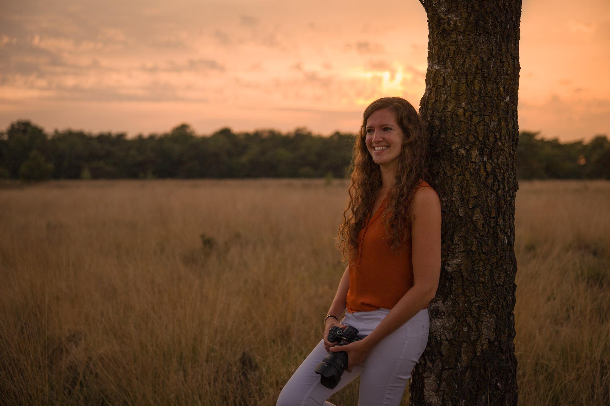 Fotografe op veld met hoog gras leunend tegen boom tijdens gouden uurtje door Mayra Fotografie