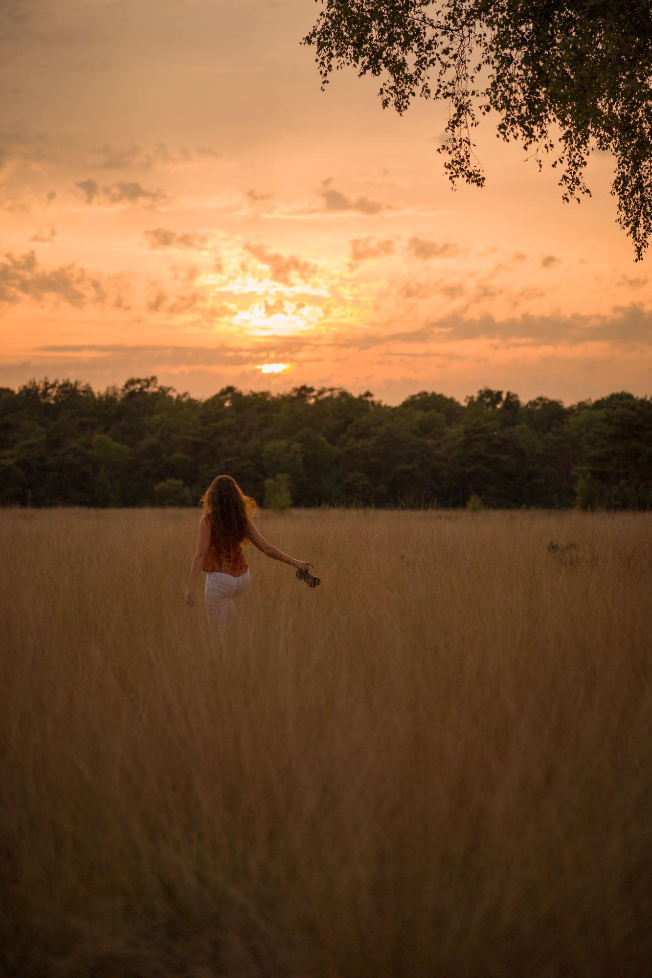 Fotografe rennend in veld met hoog gras tijdens gouden uurtje door Mayra Fotografie