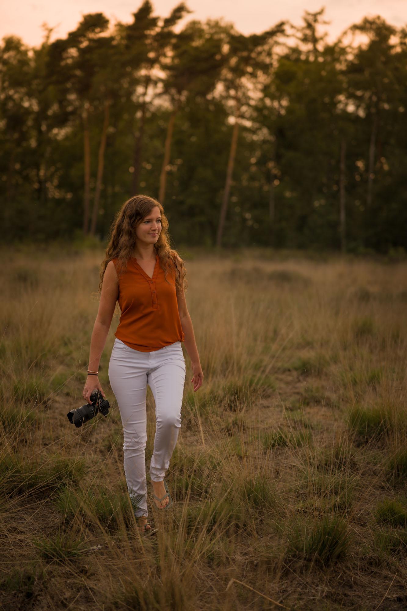 portret van fotografe tussen hoog gras tijdens gouden uur door mayrafotografie