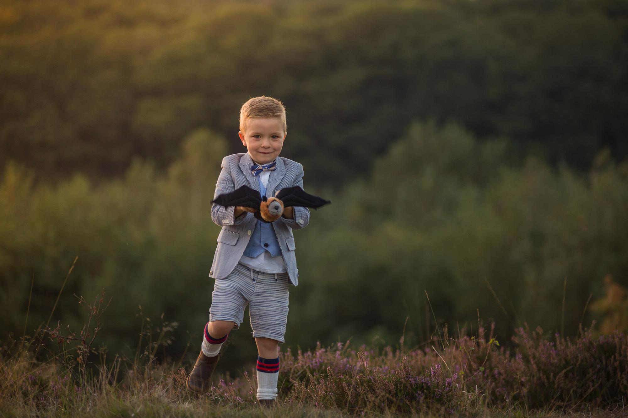 kind portret van met vleermuis spelende jongen op de heide tijdens het gouden uur door Mayra Fotografie