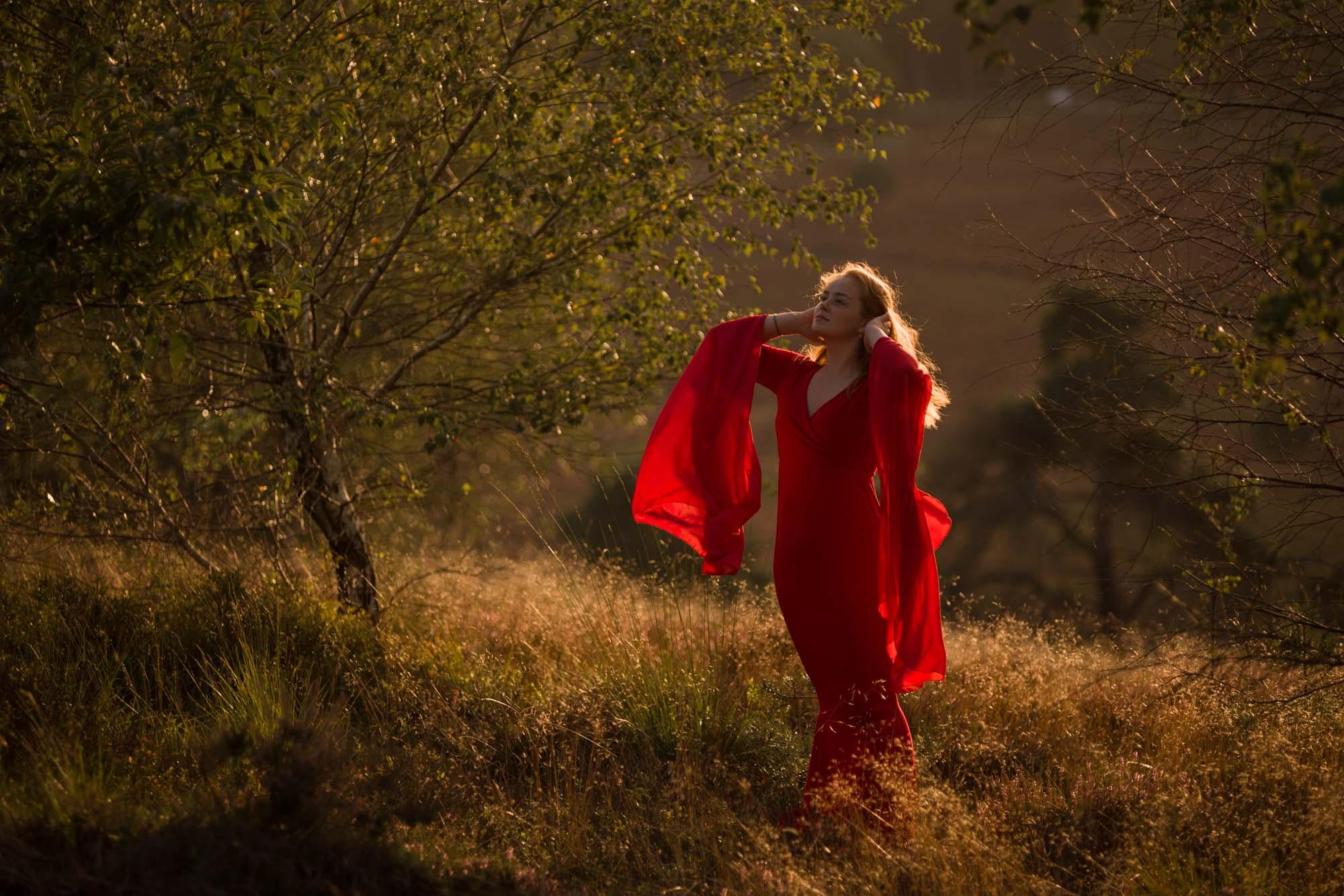 portret van vrouw met lang haar en rode jurk in gouden zonlicht op de veluwe door mayrafotografie