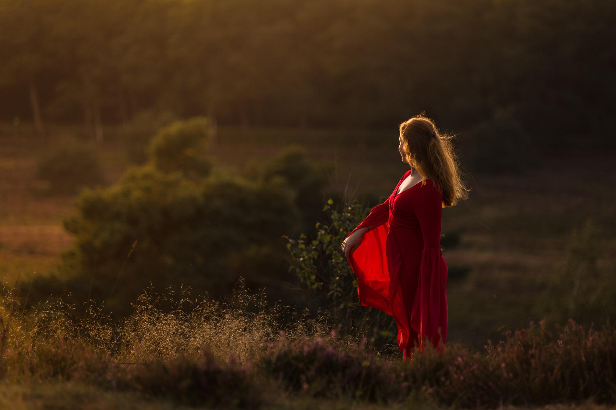 portret van jonge vrouw met rode jurk in gouden zonlicht op de veluwe door mayrafotografie