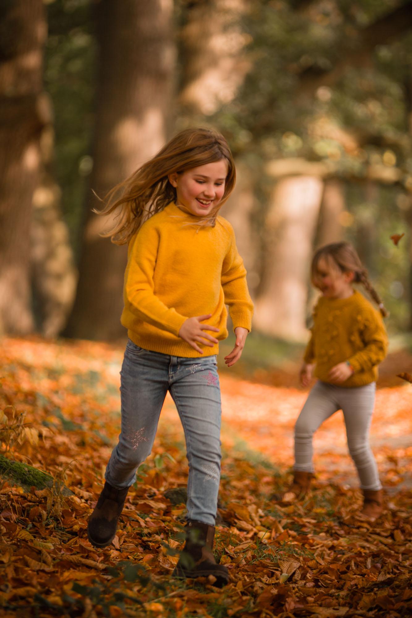 Rennende en spelende zusjes in herfstbos door mayrafotografie