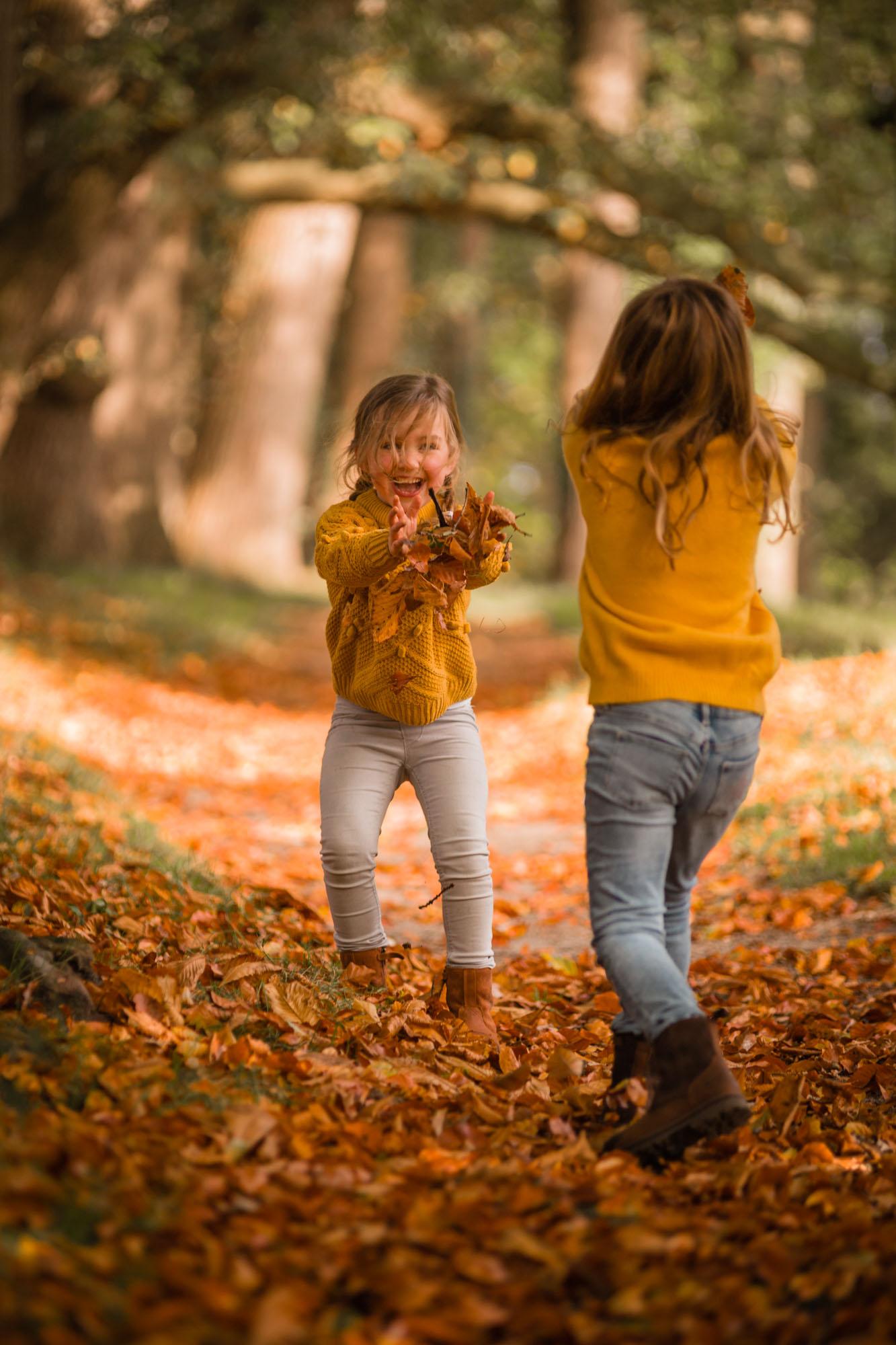 Spelende zusjes met herfstbladeren in herfst bos door mayrafotografie