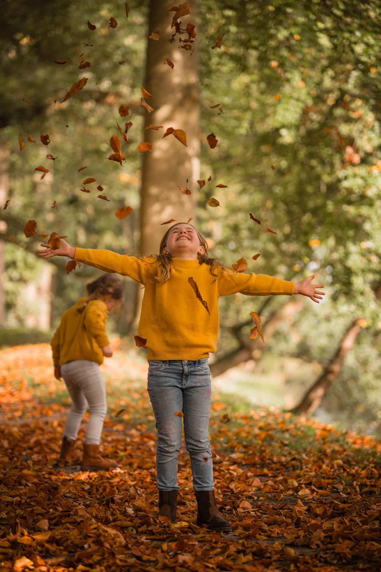 Zusjes die herfstbladeren omhoog gooien in herfst bos door mayrafotografie