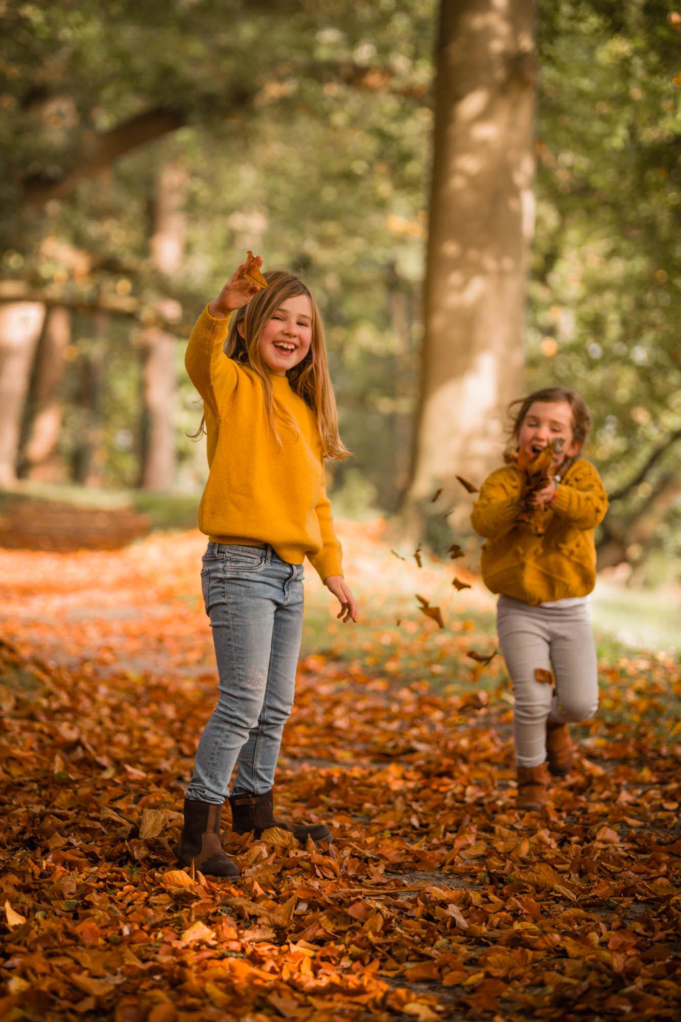 Zusjes die met herfstbladeren spelen in herfst bos door mayrafotografie