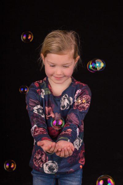 studio foto van blond meisje met bloemen shirt en bellenblaas door mayrafotografie