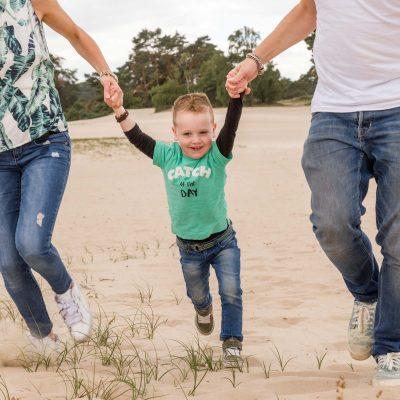 foto van rennende kleuter tussen papa en mama in bij de soesterduinen door mayrafotografie