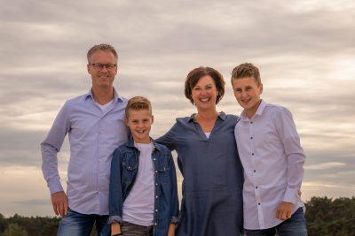 foto van lachend gezin met 2 zonen in avondlicht bij de soesterduinen door mayrafotografie