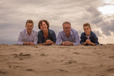 foto van liggend gezin met 2 zonen in avondlicht bij de soesterduinen door mayrafotografie