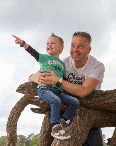 foto van zoon met vader op boomstronk door mayrafotografie