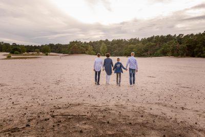 foto van wandelend gezin met 2 zonen op zandverstuiving in avondlicht door mayrafotografie