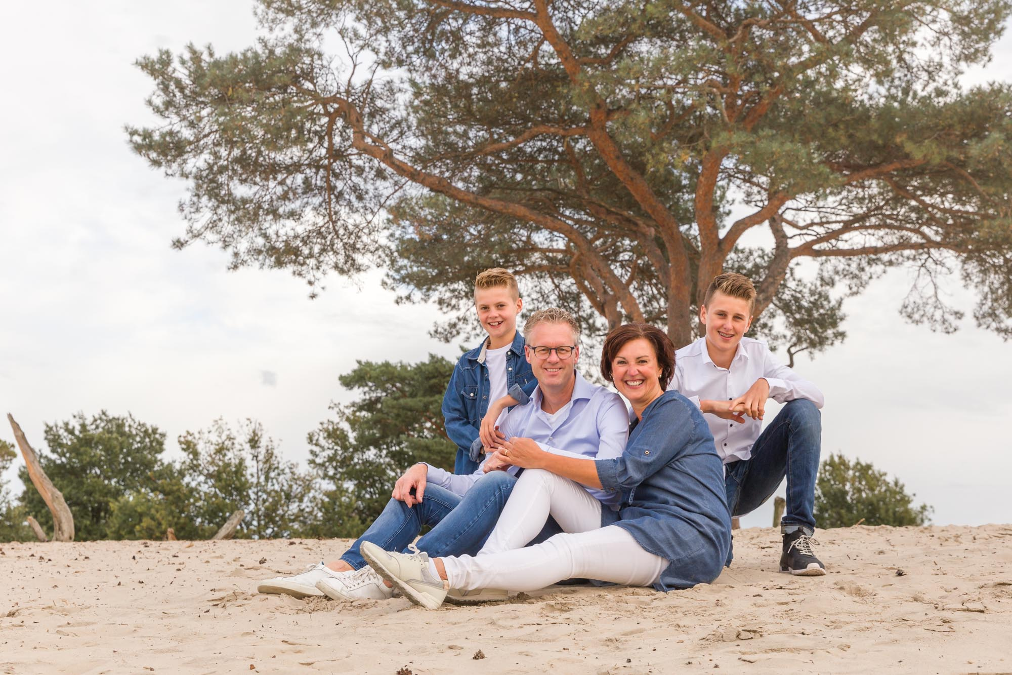 foto van zittend gezin met 2 zonen op zandvlakte door mayrafotografie
