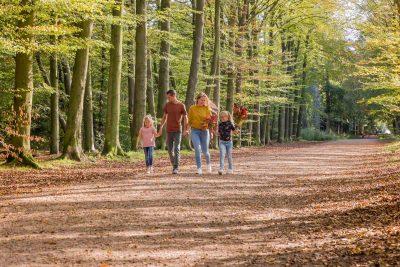 foto van gezin met 2 dochters wandelend en genietend in het bos door mayrafotografie
