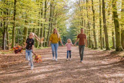 foto van gezin met 2 dochters wandelend in het bos door mayrafotografie