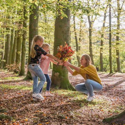 foto van 2 zusjes die moeder een herfstboeket geven in het bos door mayrafotografie