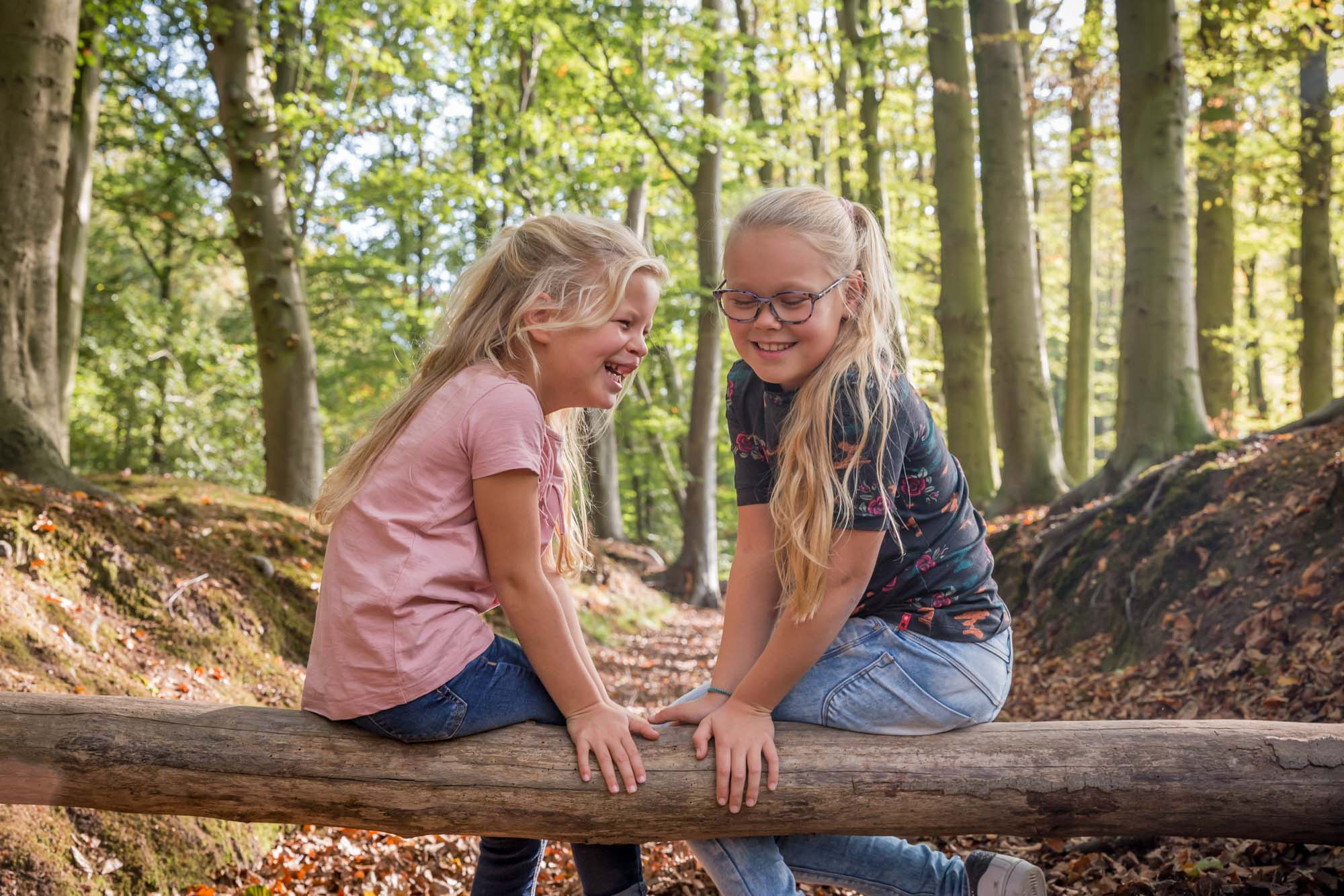 foto van 2 zusjes op een boomstam in het bos door mayrafotografie