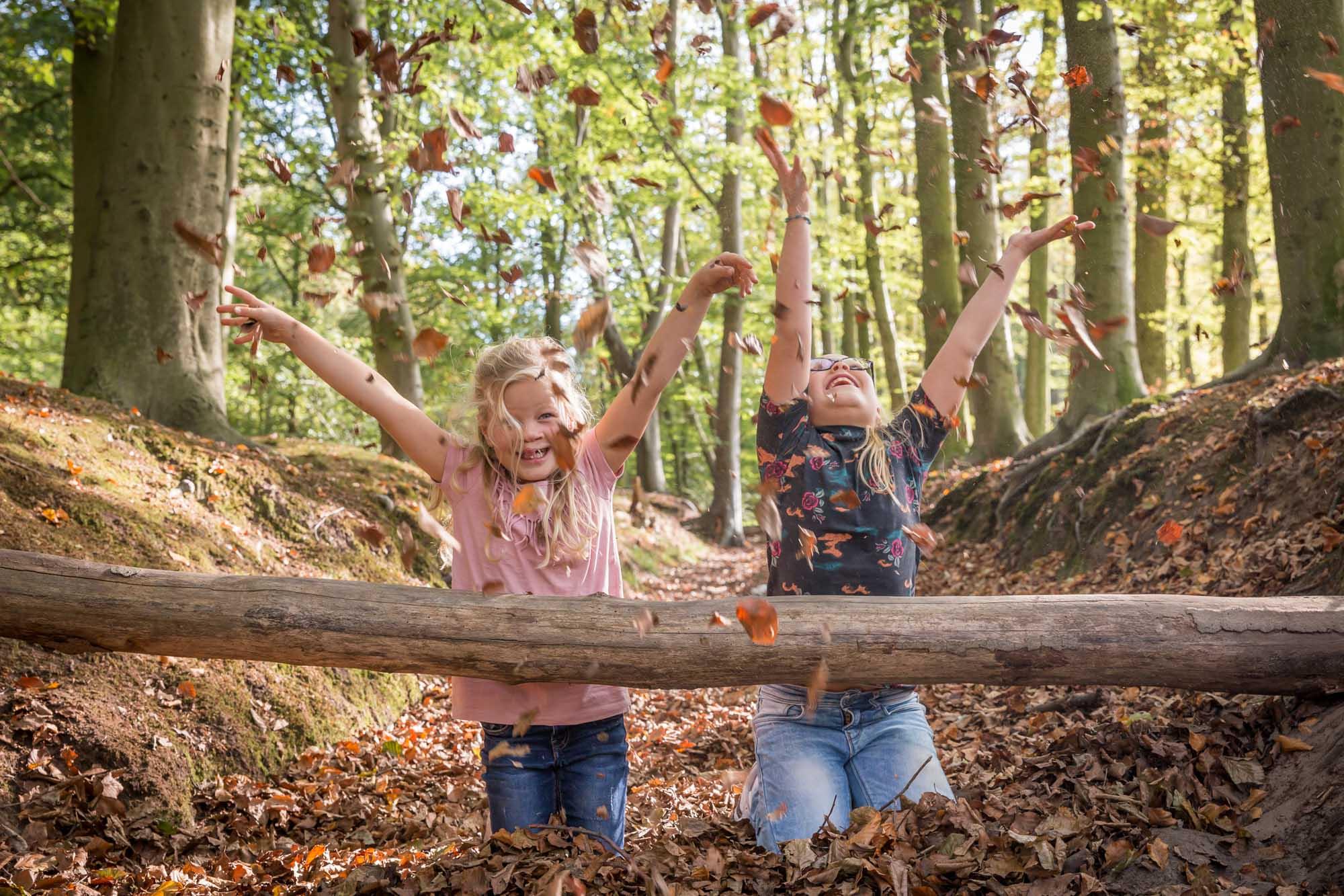 foto van 2 zusjes die gooien met herfstbladeren in het bos door mayrafotografie