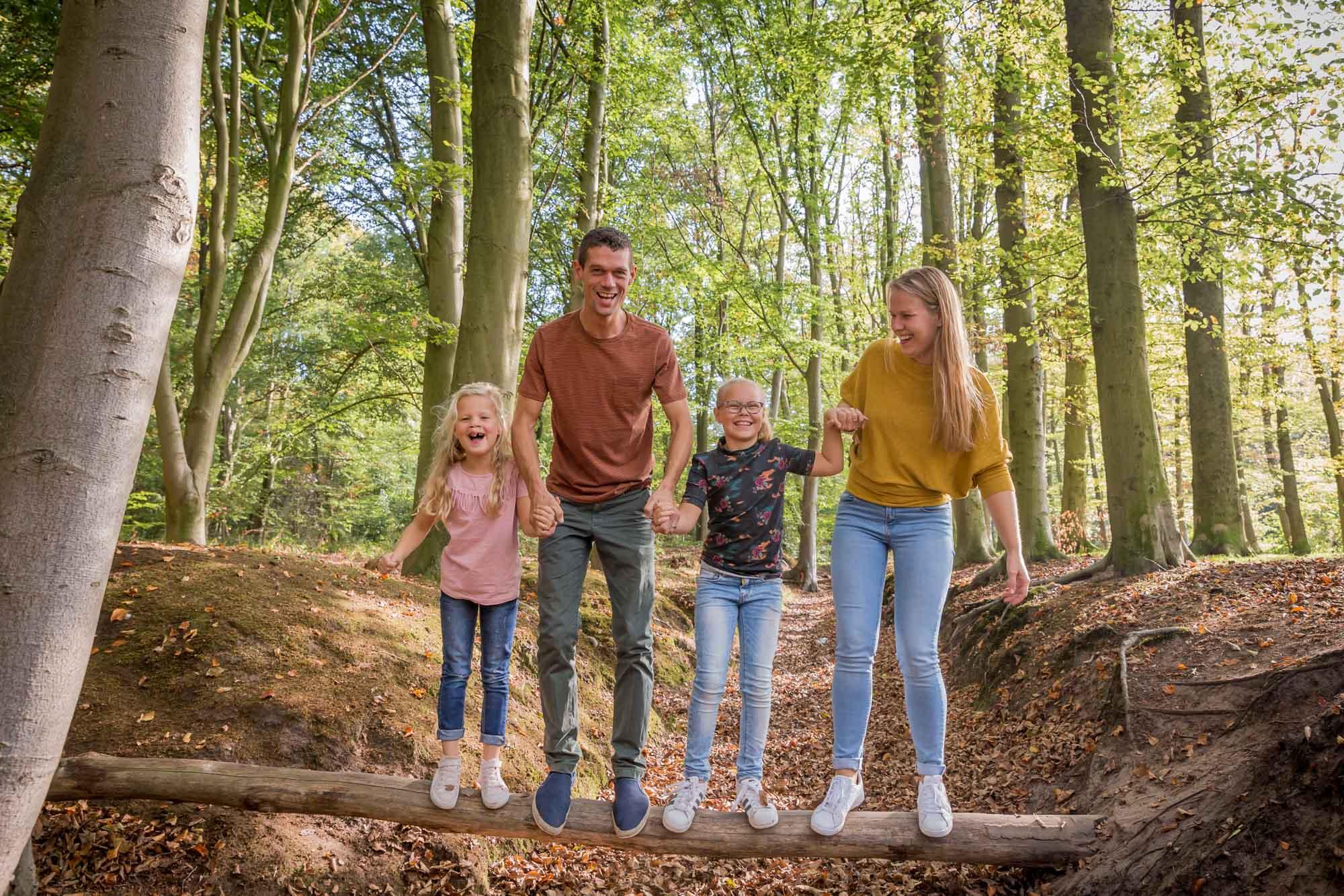 foto van gezin op boomstam in het bos door mayrafotografie