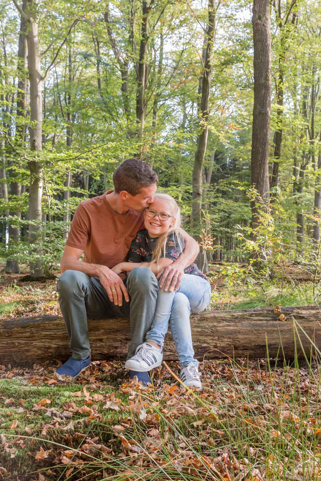 foto van vader en dochter zittend op boomstam in het bos door mayrafotografie