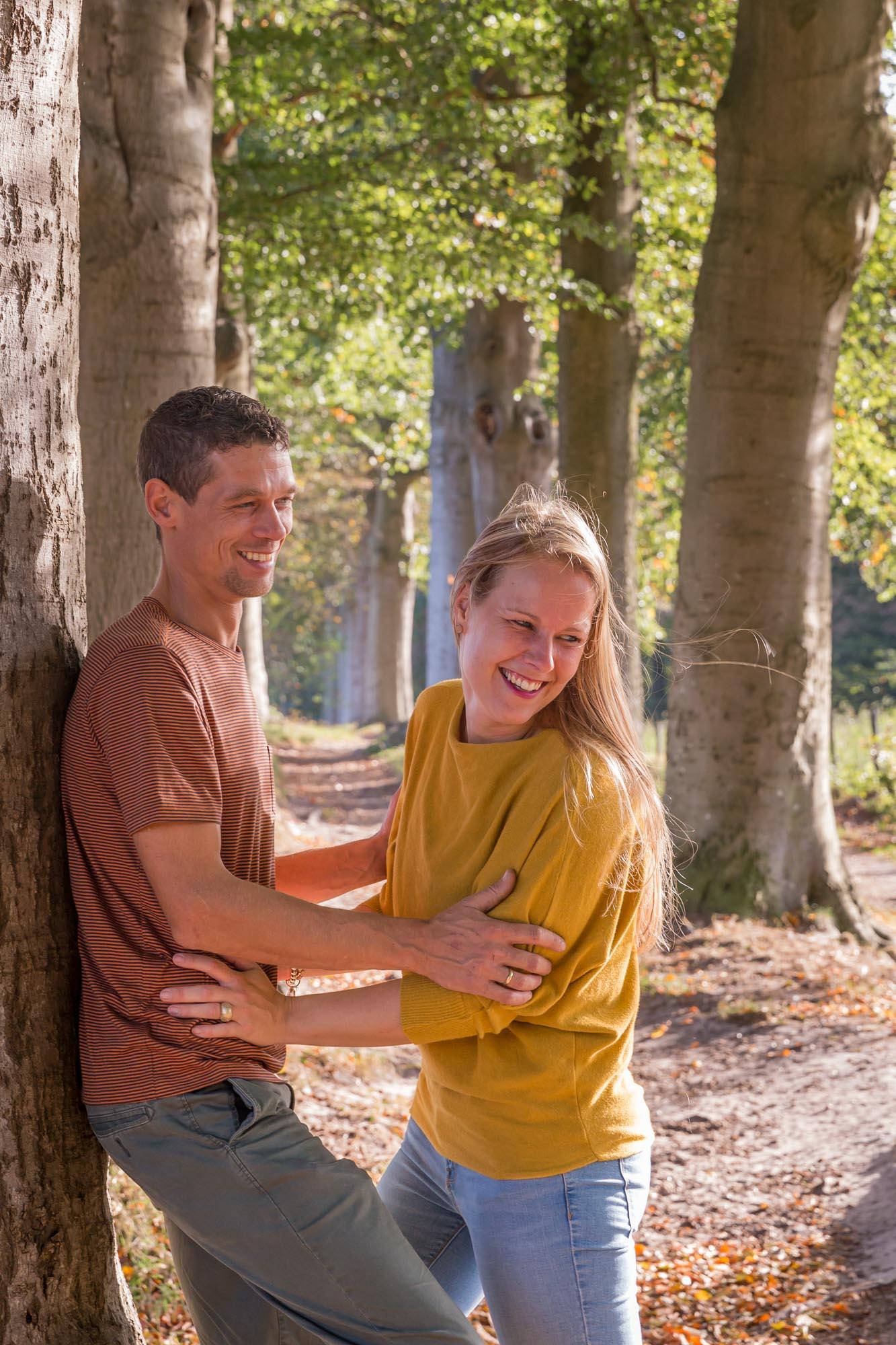 foto van ouders in het bos met herfstkleuren door mayrafotografie