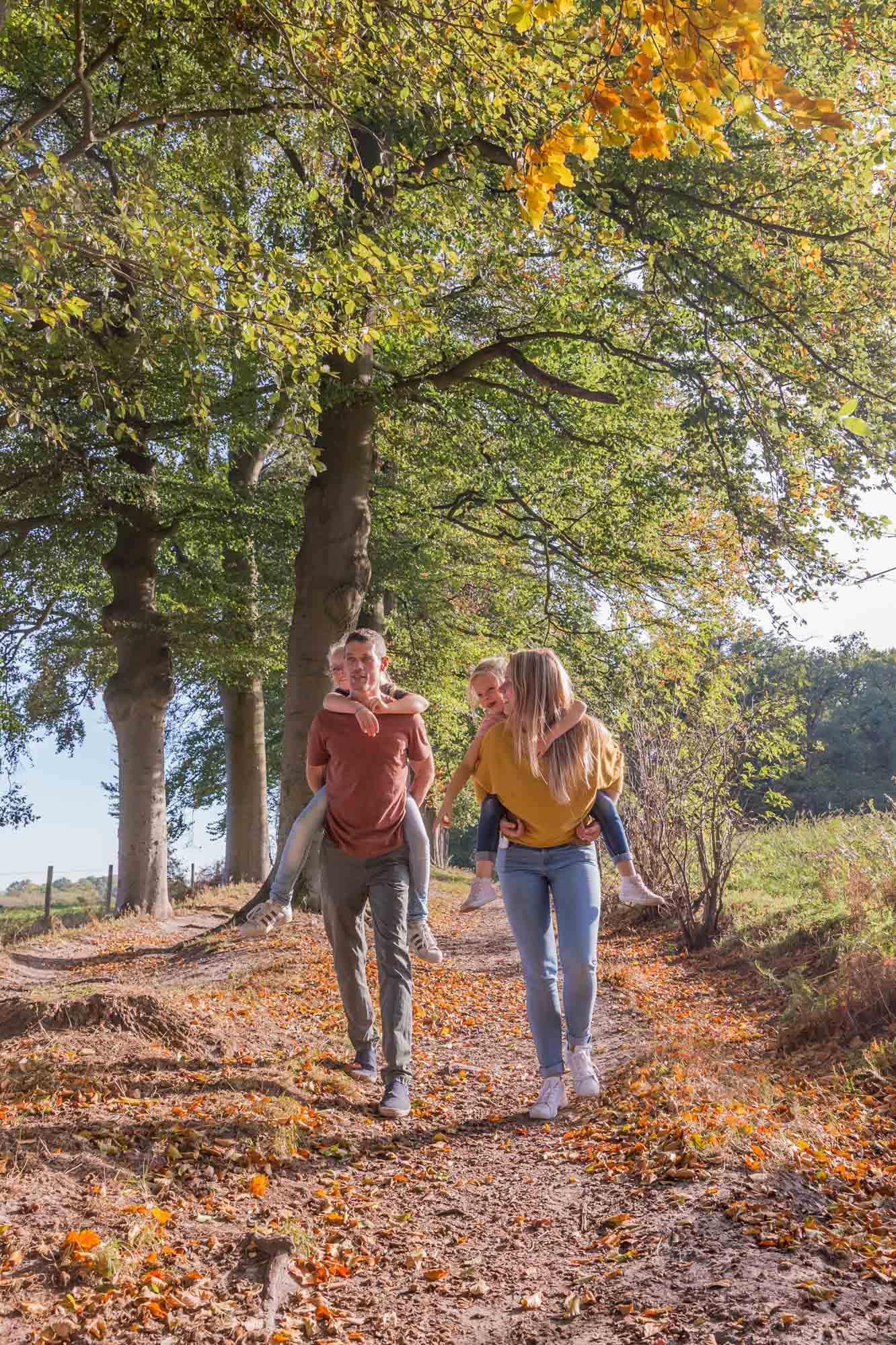 foto van ouders met kinderen op de rug in het bos met herfstkleuren door mayrafotografie