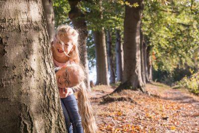 foto van 2 zusjes in het bos met herfstkleuren door mayrafotografie