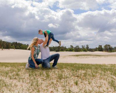 foto van stoeiend gezin op gras en zandvlakte bij de soesterduinen door mayrafotografie