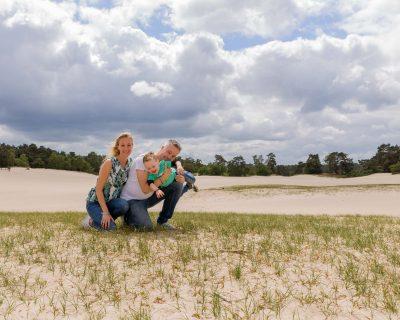 foto van stoeiend gezin op gras en zandvlakte door mayrafotografie