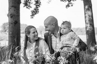 zwartwit foto van ouders met klein jongetje tussen hoog gras door mayrafotografie