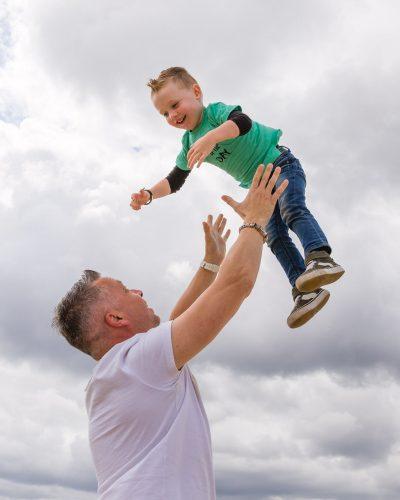 foto van vader die lachende jongen kleuter in de lucht gooit door mayrafotografie