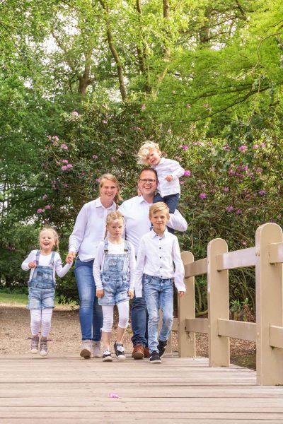foto van gezin met 4 kinderen wandelend over een brug in het park door mayrafotografie