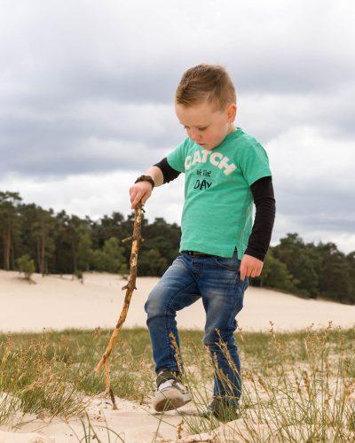 foto van jongen kleuter die met stok speelt bij de soesterduinen door mayrafotografie
