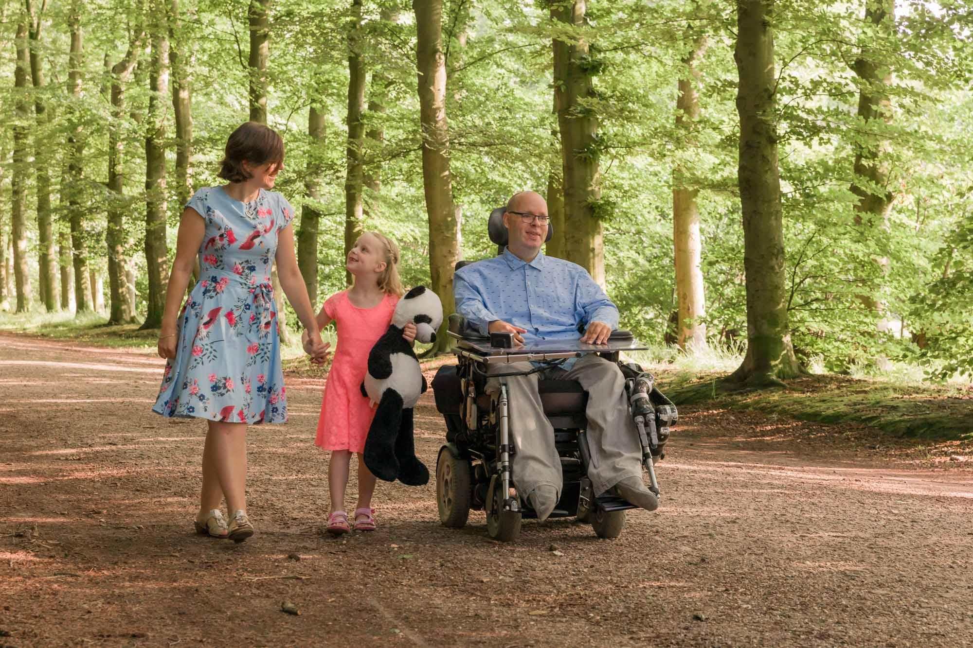 foto van vader in rolstoel en vrouw en dochter wandelend in bos door mayrafotografie