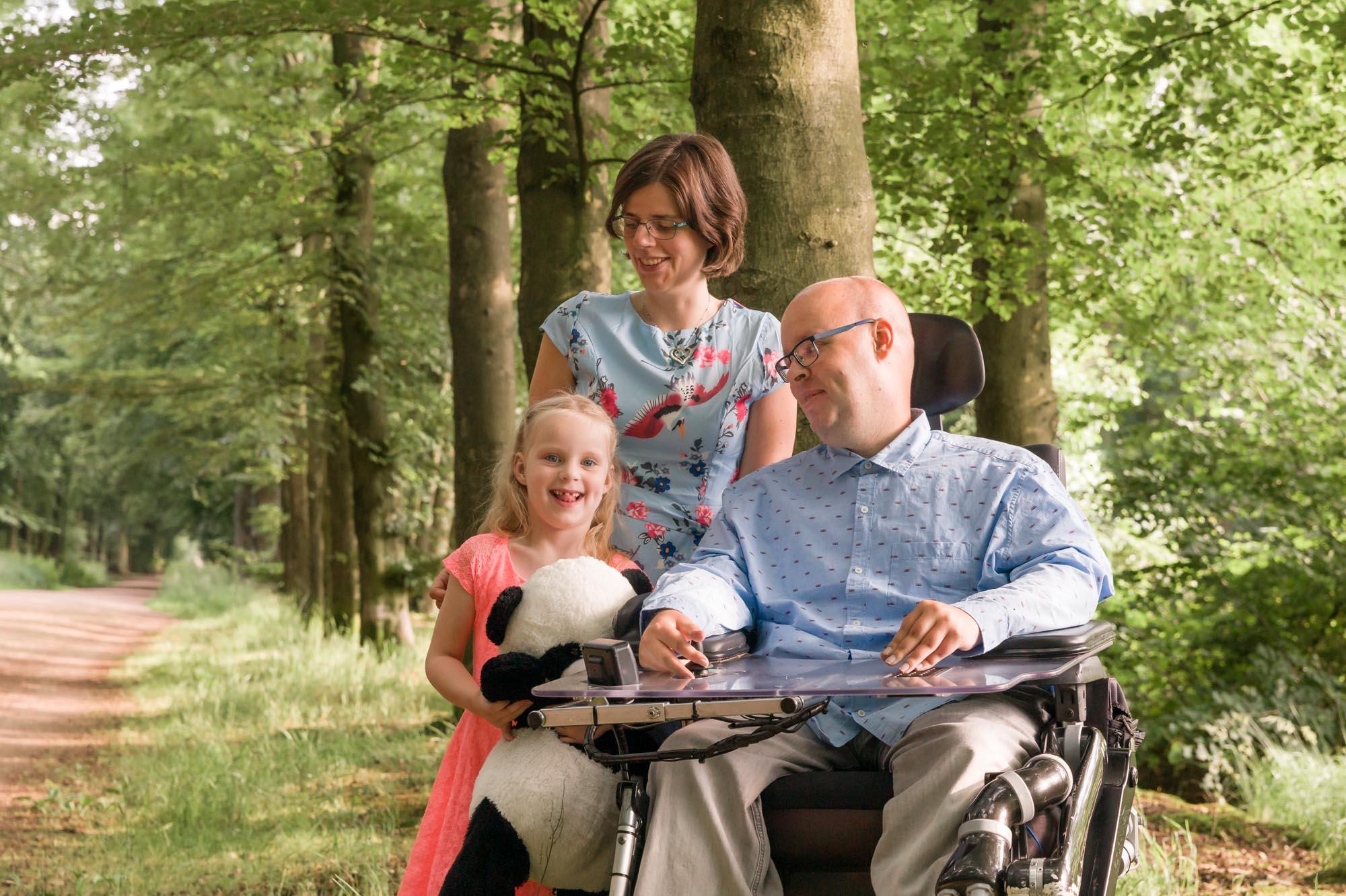 foto van vader in rolstoel en vrouw en dochter in bos door mayrafotografie