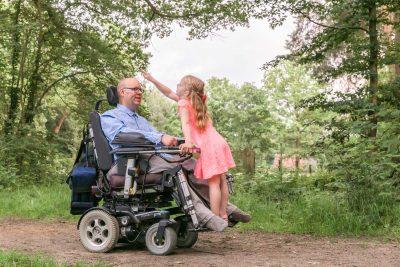 foto van vader in rolstoel en dochter in bos door mayrafotografie