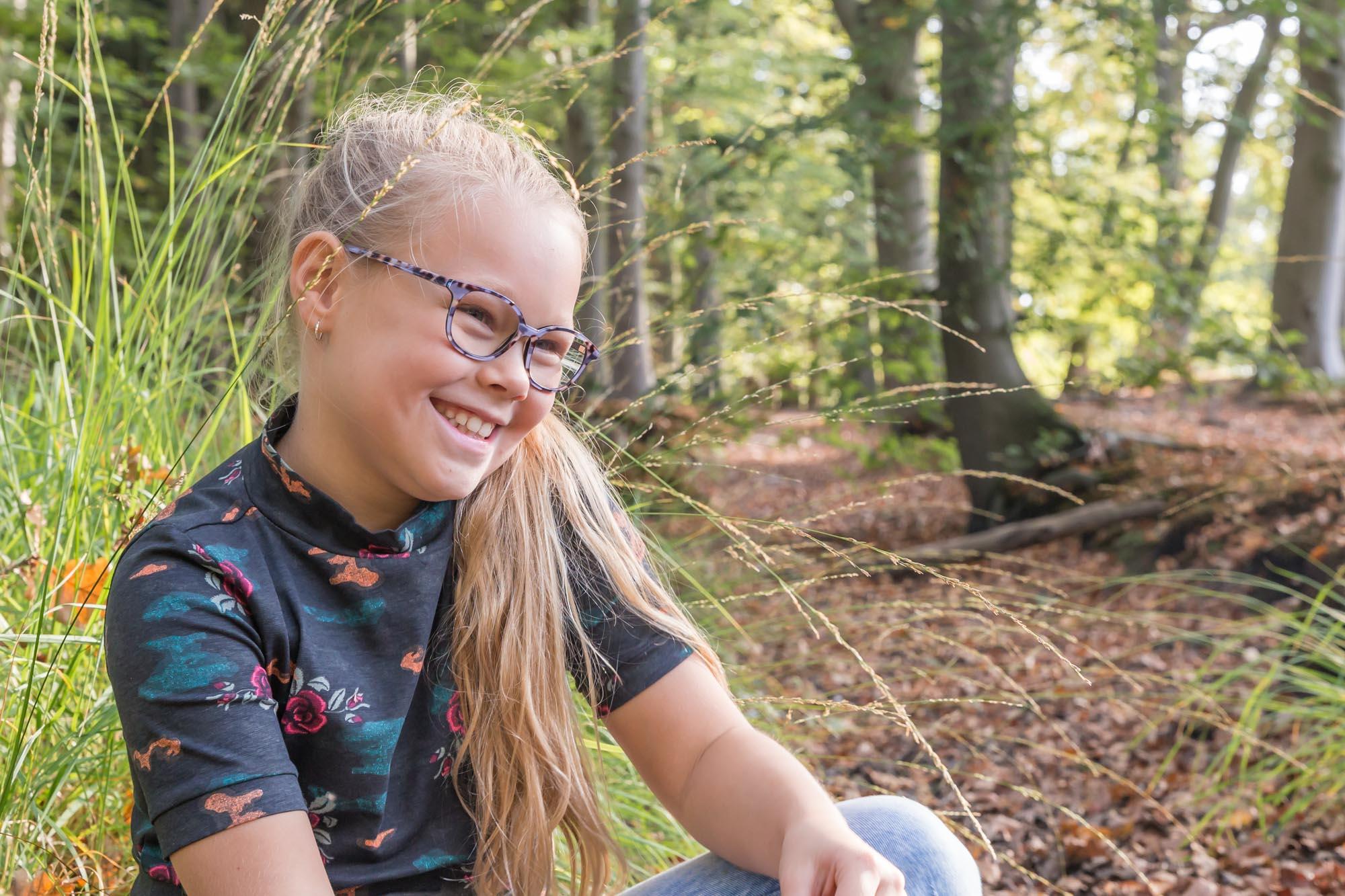 portret van blond meisje zittend bij hoog gras in bos door mayrafotografie