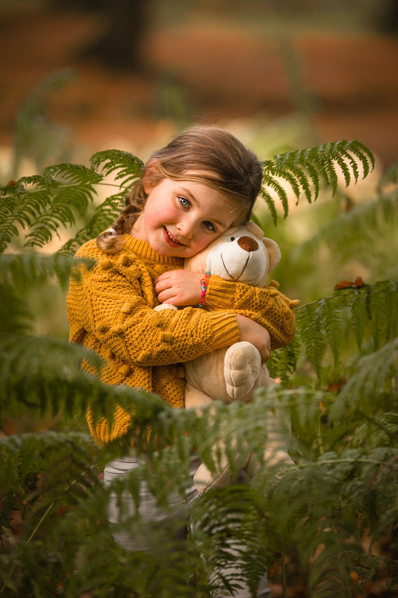 Kinderportret van jong meiske met knuffel tussen de varens door MayraFotografie