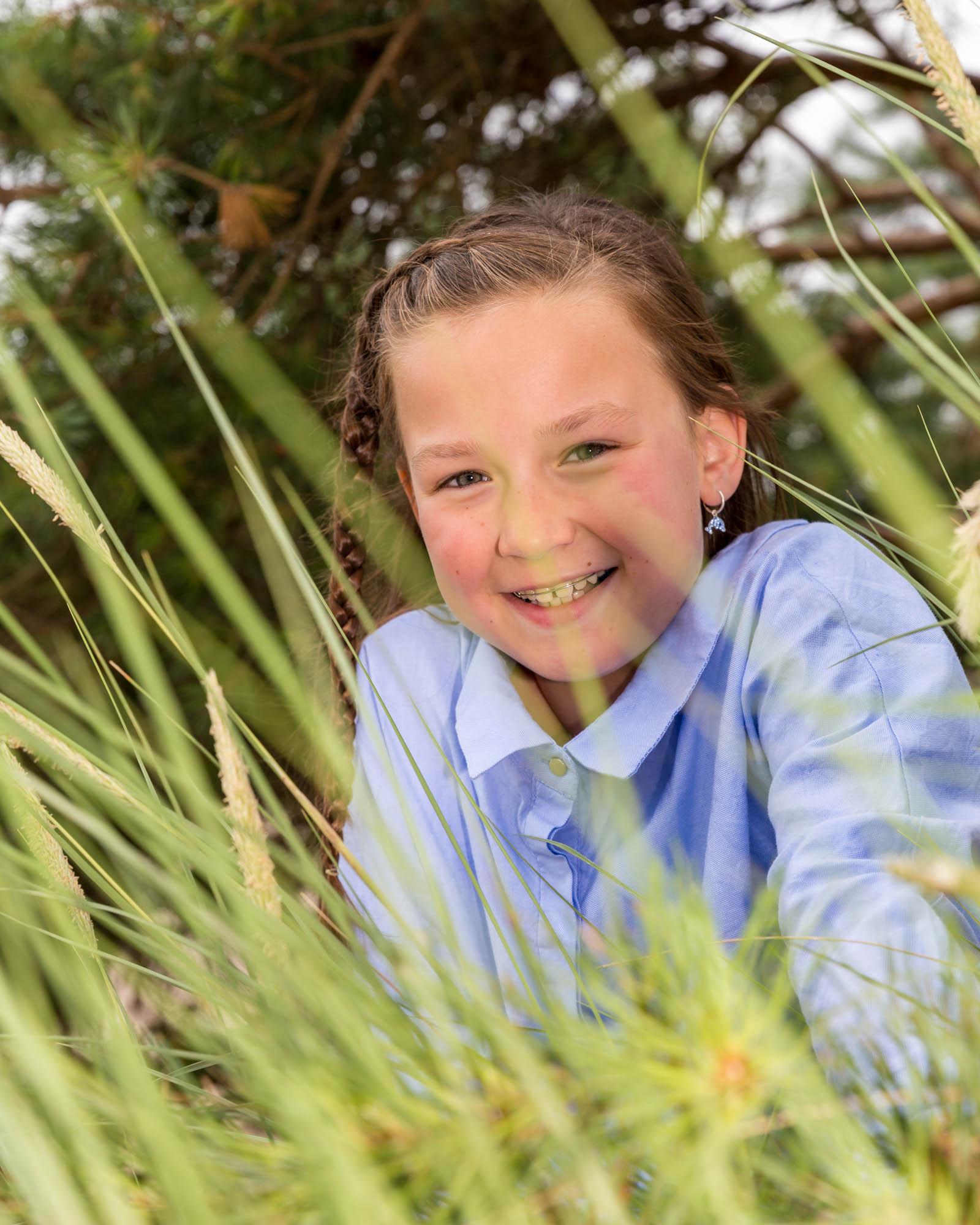 kind portret van meisje achter hoog gras door mayrafotografie