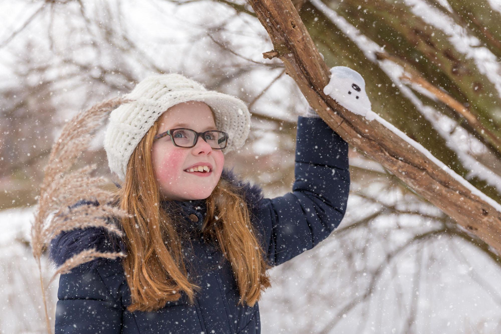 Meisje met rood haar en wollen mutsje in de sneeuw door MayraFotografie