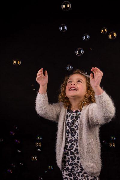 studio kinder portret foto van jong blond meisje spelend met bellenblaas door mayrafotografie