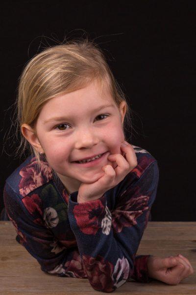 studio kinder portret foto van jong blond meisje met kin op haar hand door mayrafotografie