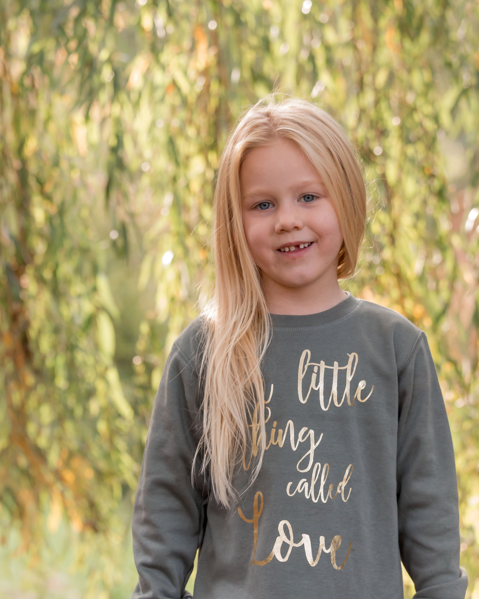 kind portret van meisje met blond lang haar tegen groene treurwilg door mayrafotografie