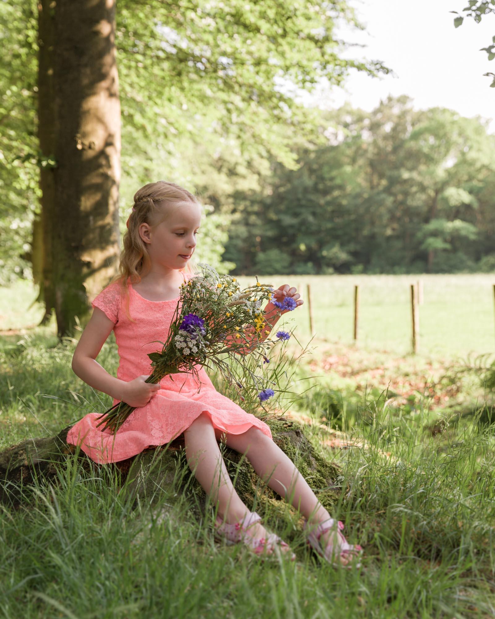 kinderportret meisje met boeket bermbloemen in het bos door mayrafotografie