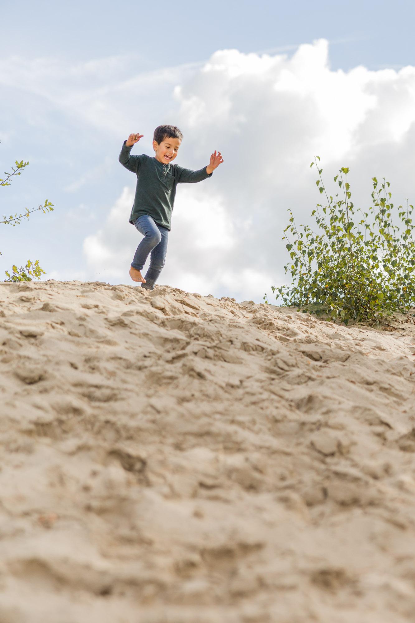 kinderportret van jongetje dat van zand heuvel af rent door MayraFotografie