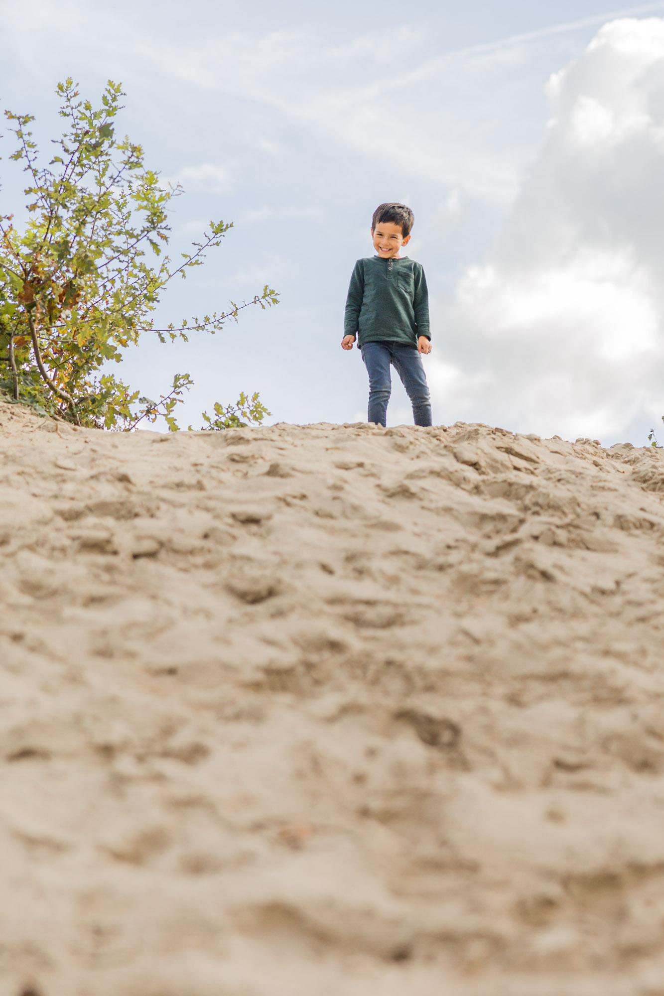 kinderportret van lachend jongetje op zandheuvel door MayraFotografie