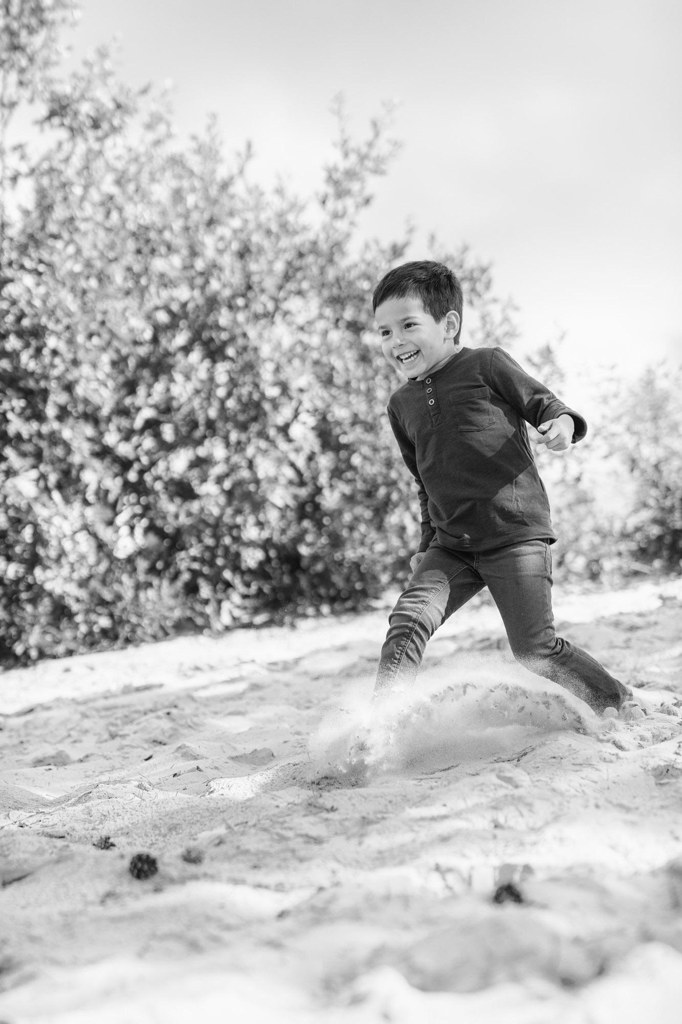 Zwart-wit kinderportret van jongetje dat van zand heuvel af rent door MayraFotografie