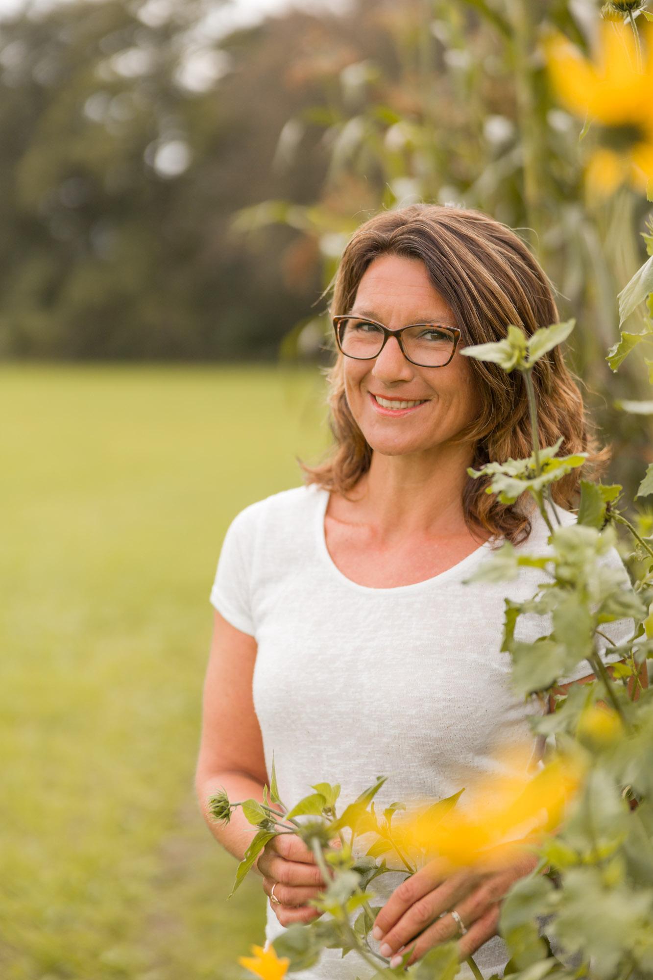 zomers portret van lachende vrouw bij zonnebloemen door MayraFotografie